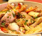 Camarão, lulas e frango com alho e piri-piri